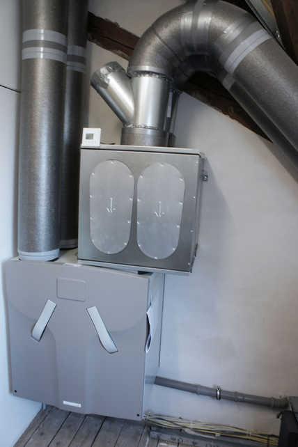 Auf dem Dachboden schlägt das Herz der zentralen Lüftungsanlage des Kenzinger Mehrfamilienhauses: Das Lüftungsgerät Zehnder ComfoAir 550 mit dem darüber liegenden Schalldämpfer für die Luftansaugung.