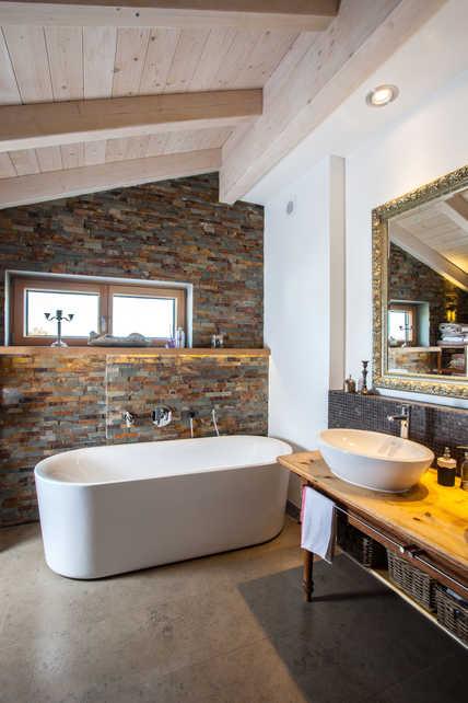 Das ästhetische Ambiente des Badezimmers wird durch das dezente Lüftungsgitter über der Badewanne nicht gestört